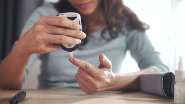 Close-up Woman Checking blood sugar with diabetes using a blood glucose meter to test blood glucose at home
