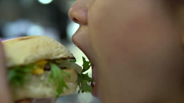 Close-up Woman eating hamberger, junk food stock