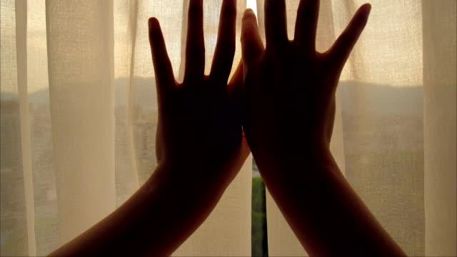 vídeos de stock e filmes b-roll de close-up woman hand open curtain - open window
