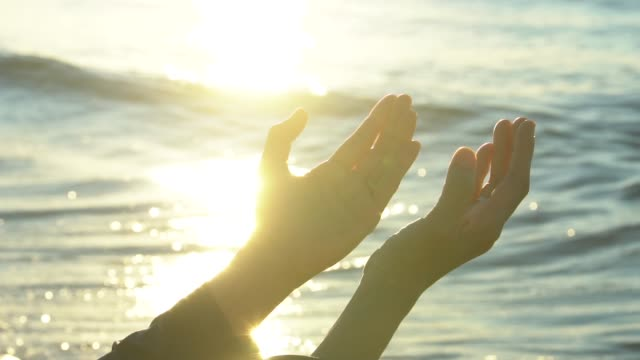 Closeup woman hands praying for blessing from god during sunset background