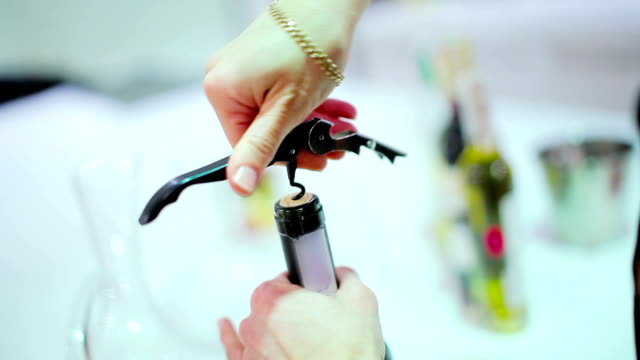 Close-up - woman open the wine bottle with corkscrew video