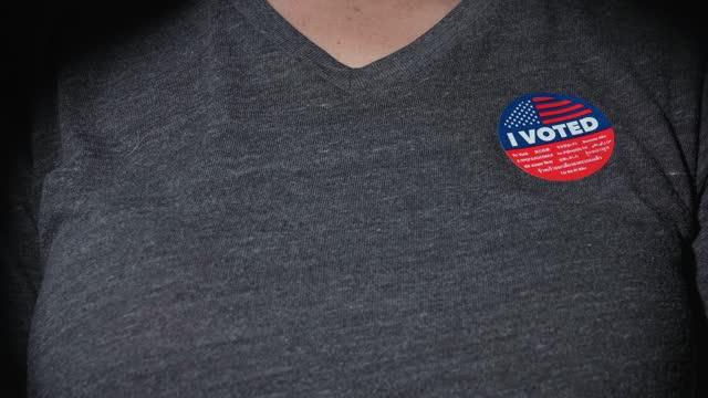 closeup woman putting I voted sticker on shirt video
