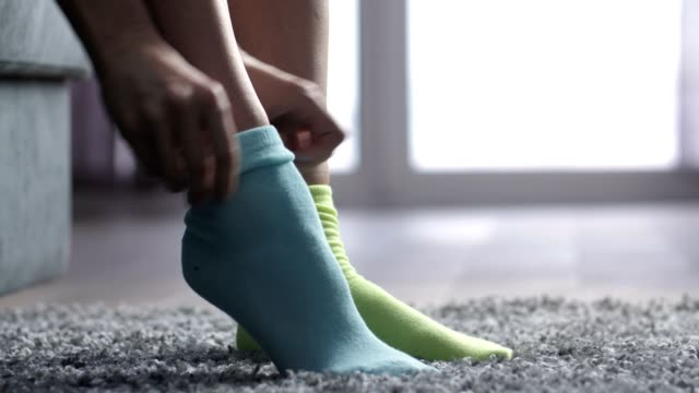 close-up woman putting on different colored socks - calzino video stock e b–roll