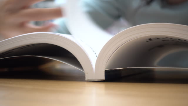 Close-up Woman reading and open book page Close-up Woman reading and open book page open book stock videos & royalty-free footage