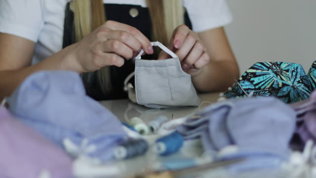 closeup woman sews medical mask at home. - cucire video stock e b–roll