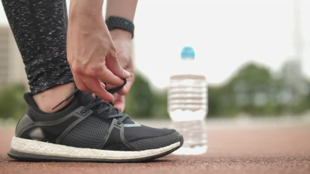 primo primo stato di primo livello donna legare la sua scarpa sportiva - annodare video stock e b–roll