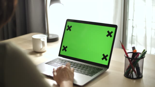 Video Close-up Woman Using Chroma key screen laptop computer on desk at home