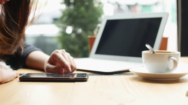 vídeos de stock e filmes b-roll de close-up woman using smart phone in cafe - coffee table