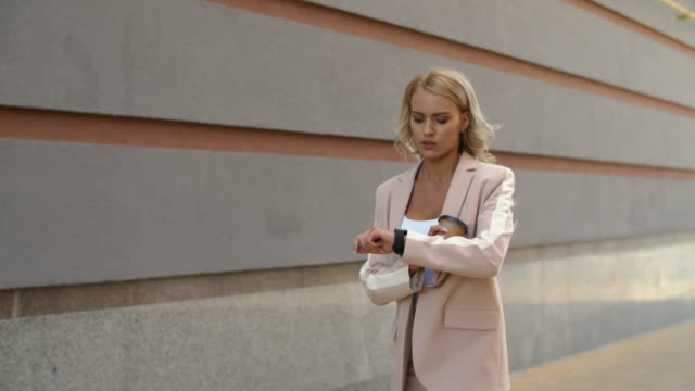 Closeup woman walking at street. Woman watching time on smart watch outdoor