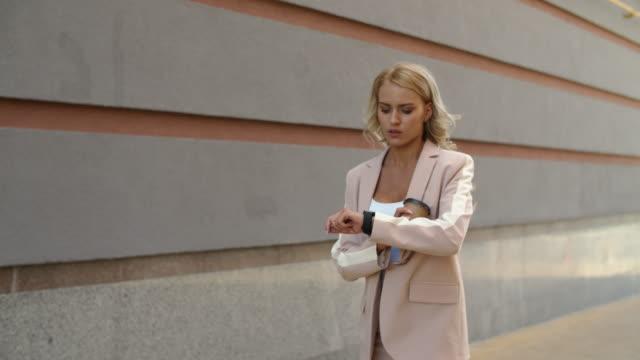 sokakta yürüyen yakın çekim kadın. akıllı saat açık saat kadın izleme - sarı saç stok videoları ve detay görüntü çekimi