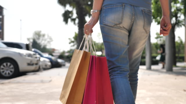 Close-up Woman walking to Car with Shopping Bag after Shopping