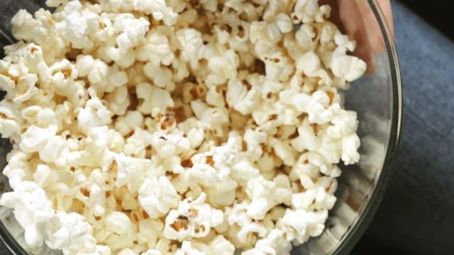 closeup woman's hand taking popcorn from transparent bowl, top view - pop corn video stock e b–roll