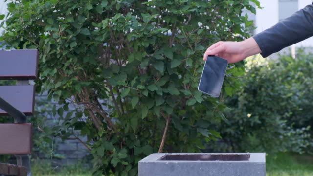 vidéos et rushes de la main de la femme de plan rapproché jette le smartphone cassé dans la poubelle - lancer