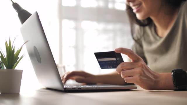 evde dizüstü bilgisayarüzerinde kredi kartı kullanarak yakın çekim kadının eli - sipariş vermek stok videoları ve detay görüntü çekimi
