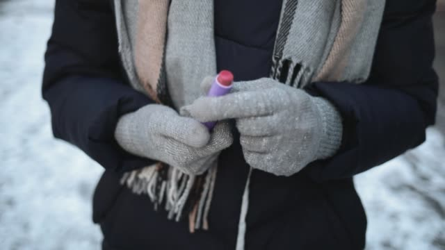 vídeos de stock e filmes b-roll de close-up woman's hands get lipstick from pocket to apply on lips while standing on snowy street in city in winter. - brilho labial