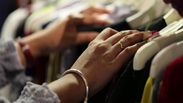 vídeos de stock, filmes e b-roll de mãos de mulher closeup olhando através de cremalheira, câmera lenta - boutique