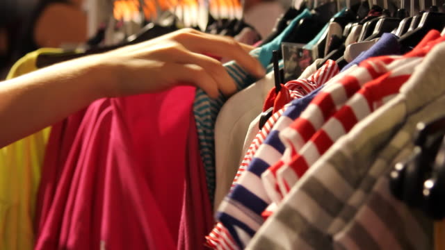 Closeup woman's hands looking through clothes rack A close up of a woman's hand looking through vibrant shirts on a clothes rack in a clothing store. buying stock videos & royalty-free footage