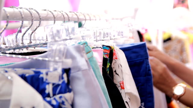 Closeup woman's hands looking through clothes rack video