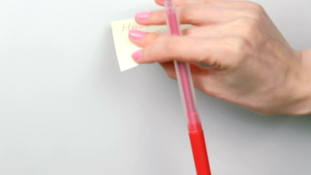 Closeup woman's hands stick yellow sticker paper sheets with words have a fun. video