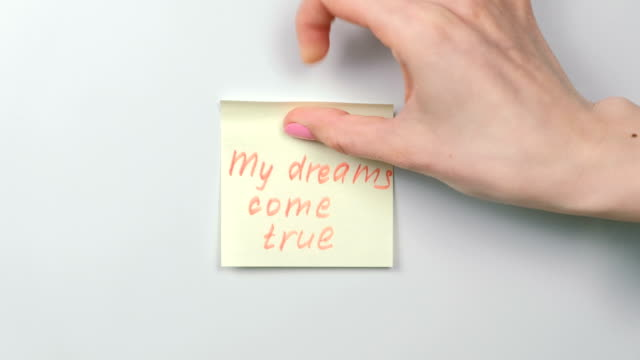 Closeup woman's hands stick yellow sticker paper sheets with words my dreams come true. video