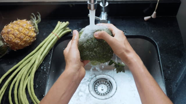 close-up woman's hands washing broccoli at domestic kitchen - broccolo video stock e b–roll