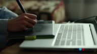 istock closeup womans hands with pen tablet and laptop. woman freelancer retoucher working at home 1195167987