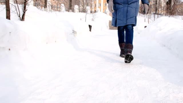 le gambe della donna da vicino camminano nel parco invernale della città durante il giorno con il tempo nevoso con neve che cade. vista frontale. - dorso umano video stock e b–roll