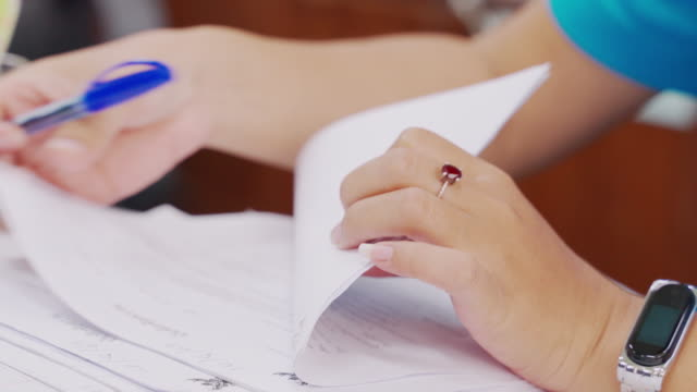 Close-up women are reviewing accounting documents in the preparation of financial statements.