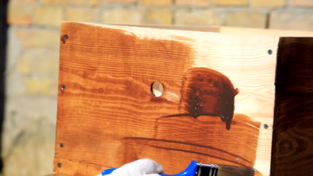 Close-up Wood painting with a brush with the brown color video