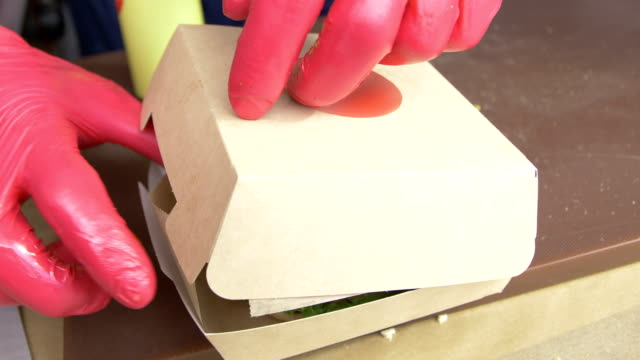 closeup worker packs hamburger in karton box for delivery - handschuh stock-videos und b-roll-filmmaterial