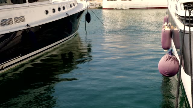 close-up. yachts are anchored in a marina. fenders hang on their sides - molo video stock e b–roll