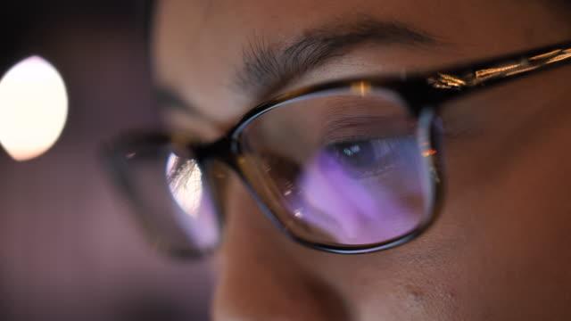 クローズアップ若いアジアの女性の目は、コンピュータ上で作業し、ラップトップのモニターを見て - pc 画面点の映像素材/bロール