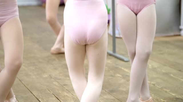 closeup , Young ballerina legs in ballet shoes, pointes, in beige leotards, perform exercises near barre, on an old wooden floor in a ballet school, during ballet lesson
