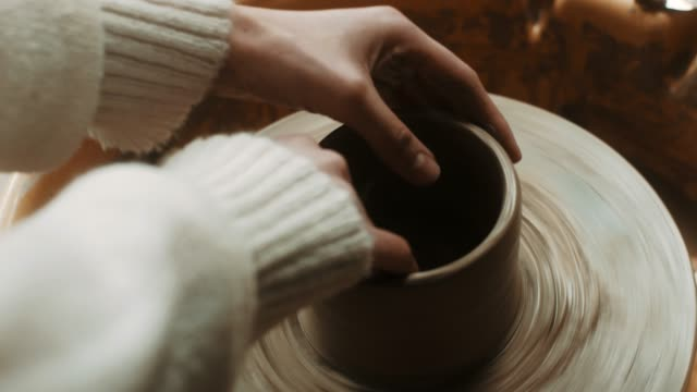 Close-up, young beautiful woman using pottery wheel at atelier video