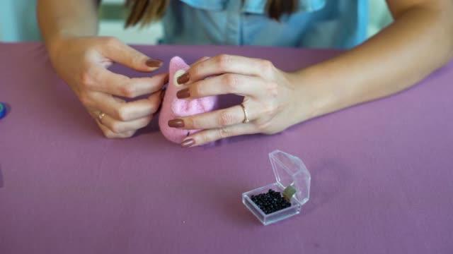 closeup young caucasian woman hands making wool dry felting tutorial - feltro video stock e b–roll
