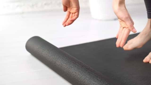 close-up giovane donna in forma mani rotolamento tappeto yoga grigio prepararsi per fare esercizi mattutini a casa - materassino ginnico video stock e b–roll