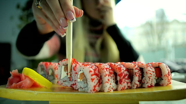Close-Up Young Girl Eating Sushi with Chopsticks in a Restaurant video