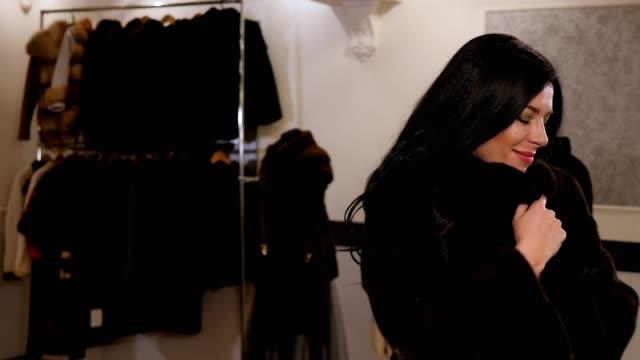 närbest i närheten ung glad kvinna som försöker på en minkrock i en pälsaffär för kvinnor. - aftonklänning bildbanksvideor och videomaterial från bakom kulisserna