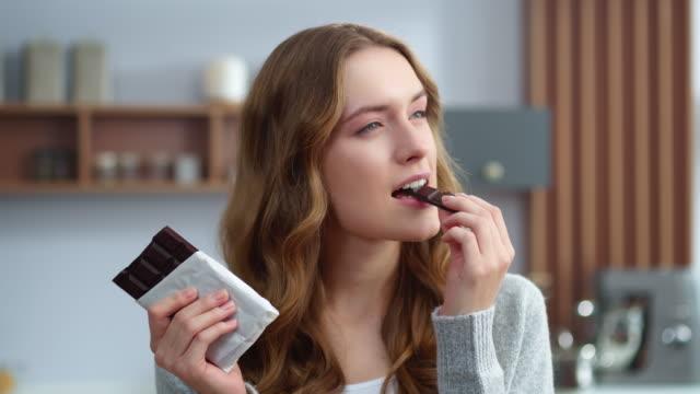 vídeos de stock, filmes e b-roll de close-up jovem mulher comendo chocolate na cozinha. garota relaxada desfrutando de chocolate - chocolate