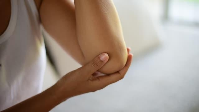vídeos de stock, filmes e b-roll de closeup jovem sentado no sofá e sentimento cotovelo dor e ela seu cotovelo em casa de massagem. conceito de saúde e médico. - articulação humana