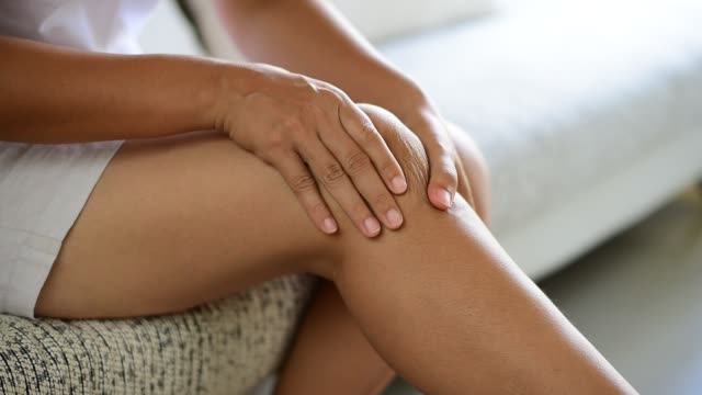 Closeup young woman sitting on sofa and feeling knee pain and she massage her knee at home. Healthcare and medical concept. Closeup young woman sitting on sofa and feeling knee pain and she massage her knee at home. Healthcare and medical concept. knee stock videos & royalty-free footage