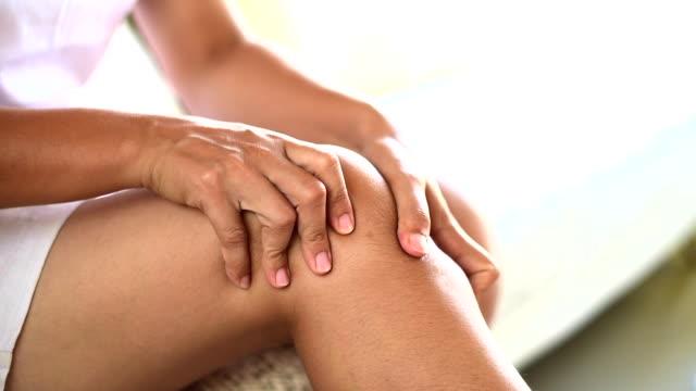 vídeos de stock, filmes e b-roll de closeup jovem sentado no sofá e sentimento joelho dor e ela o joelho em casa de massagem. conceito de saúde e médico. - perna termo anatômico