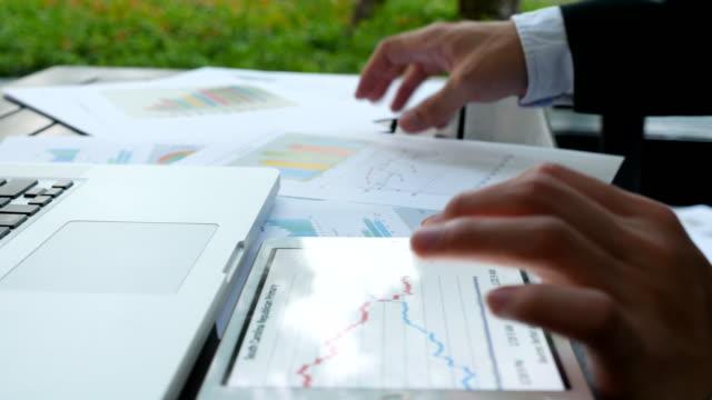 Primer plano: Dolly Shot: analistas financieros Consultar tablas y los gráficos de la pantalla - vídeo