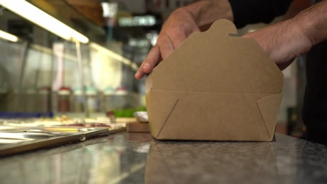 Closing a paper box for food delivery Closing a paper box for food delivery - real time 4k video food stock videos & royalty-free footage