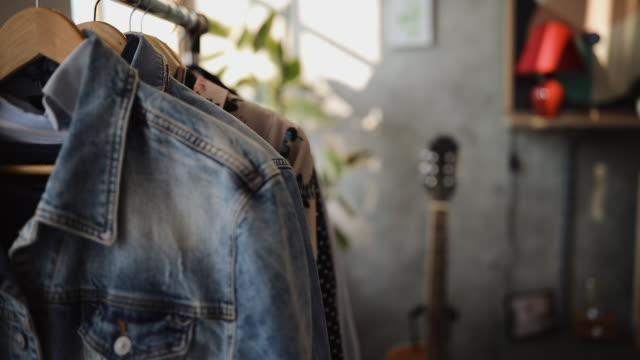 clothes hanging on clothing rack - dżinsy filmów i materiałów b-roll