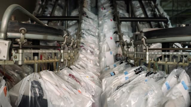 Clothes hanging on conveyor belt on movement at an industrial laundry service