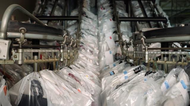 vídeos de stock, filmes e b-roll de roupa que pendura na correia transportadora no movimento em um serviço de lavanderia industrial - vestido
