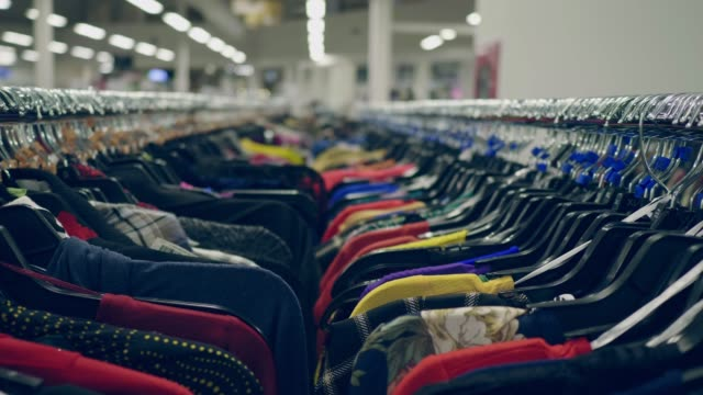 Clothes on a coat rack Hanger with new t-shirts in a clothing store department store stock videos & royalty-free footage
