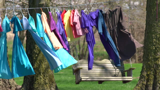 Clothes on the Line Drying Outside Near Swing Bench Colorful Womens Dresses