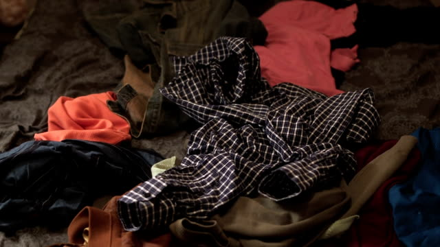Clothes thrown on a pile of clothes in bed video